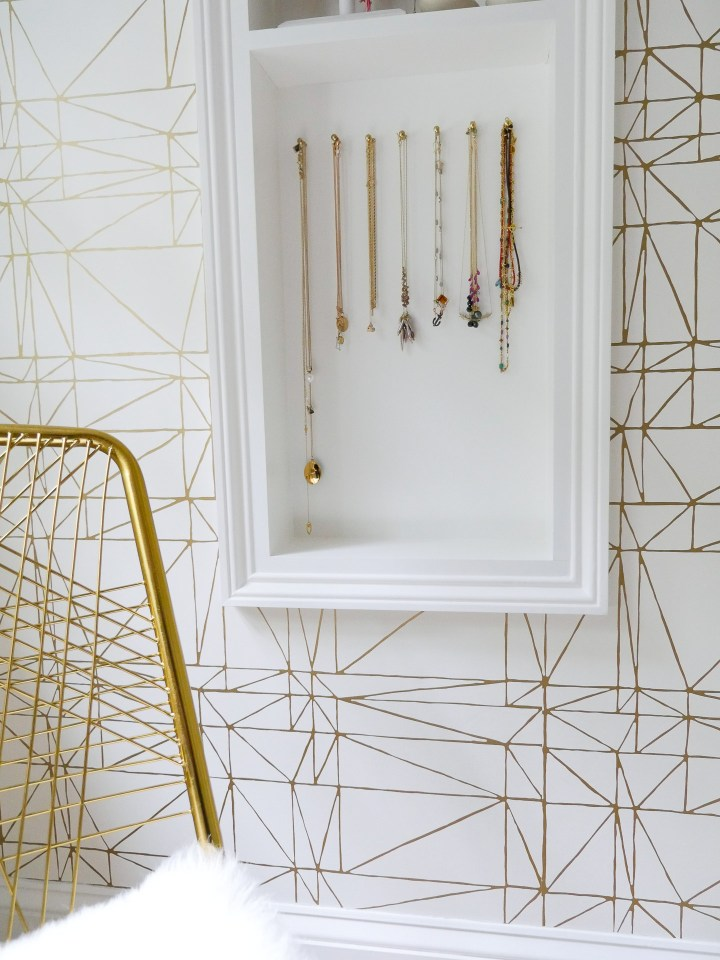 A close up of the necklace display in Eva Amurri Martino's glam room in her connecticut home featuring various gold necklaces