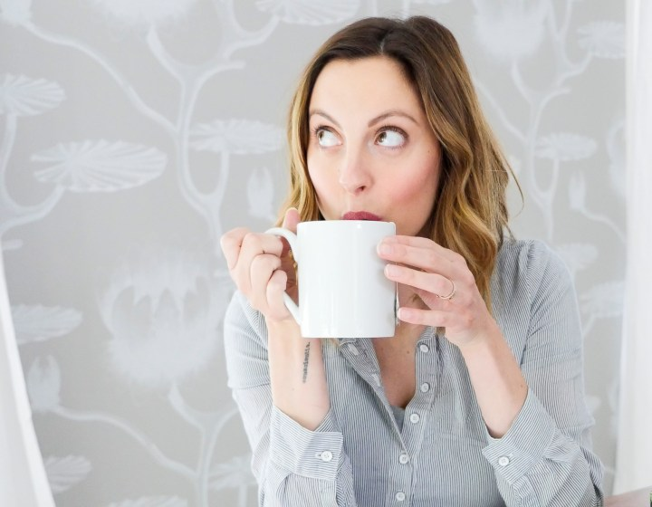 Eva Amurri Martino of lifestyle blog Happily Eva After sipping hot tea from a white mug while sitting in her dining room with a backdrop of grey and white patterned wallpaper
