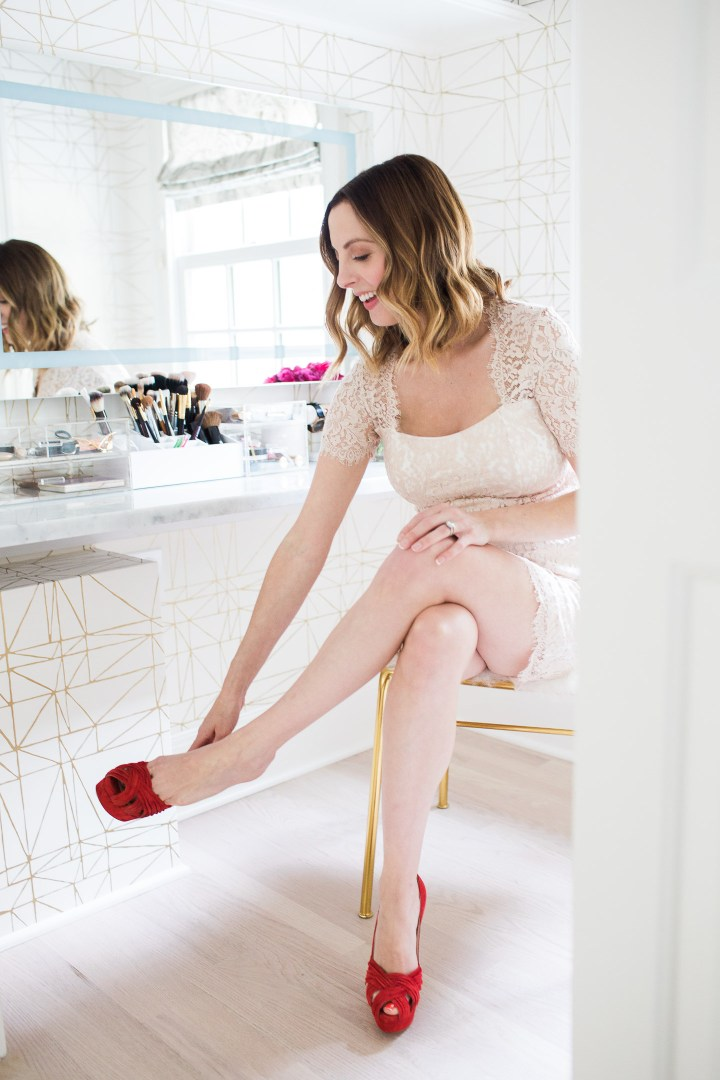 Eva Amurri Martino of lifestyle and motherhood blog Happily Eva After wearing a nude lace maternity dress and sitting at the table in her Glam Room putting on a pair of red suede louboutin platform pumps
