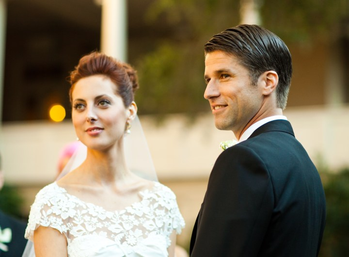 Eva Amurri Martino of lifestyle and motherhood blog Happily Eva After, wearing a white wedding dress with flower applique detail while holding hands with husband Kyle Martino wearing a black Brioni Tuxedo in Charleston South Carolina