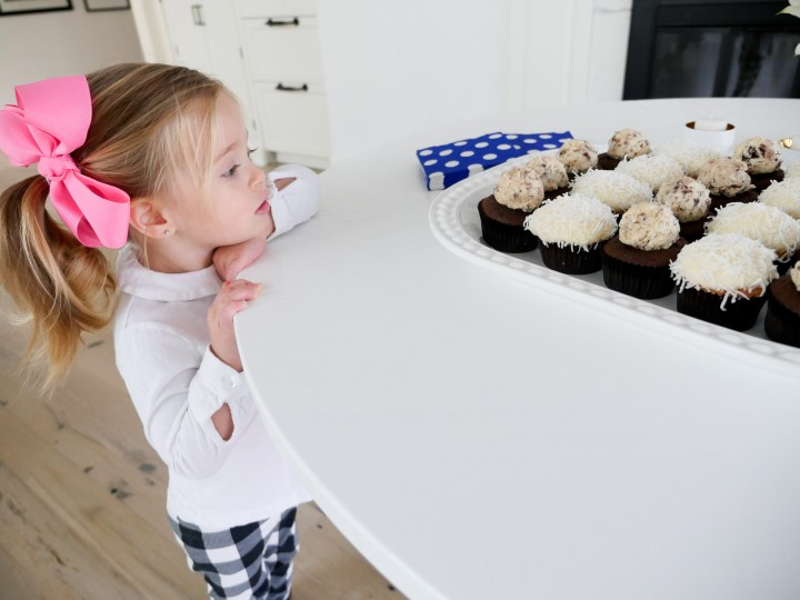 Marlowe Martino wearing a white shirt and big pink bow, eyeing a tray of cupcakes