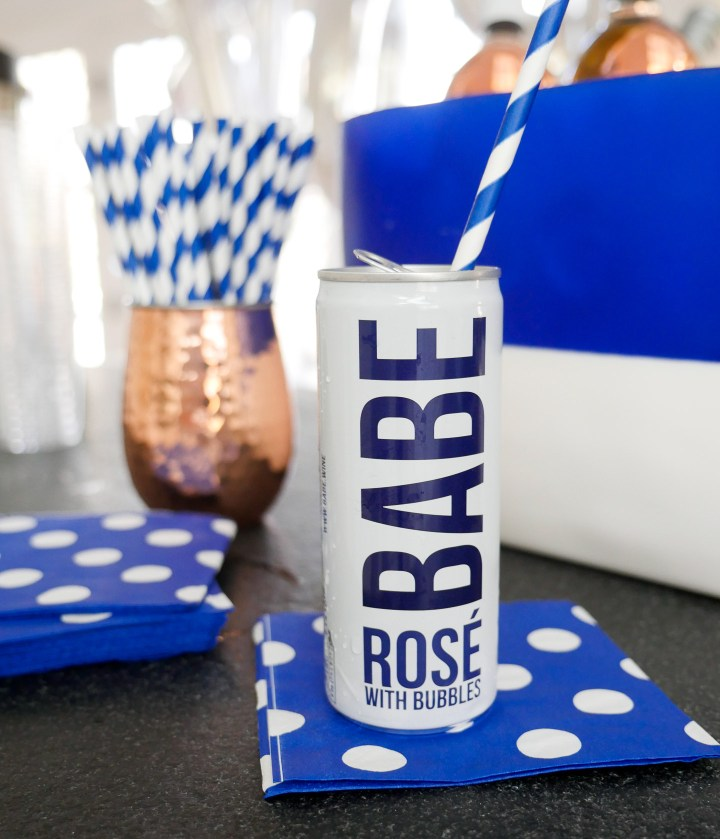 Babe Rose with bubbles pictured on a blue and white polka dot napkin with a blue and white striped straw