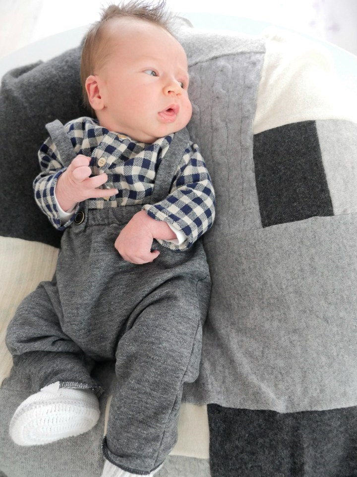 Major James Martino wearing grey overalls and a black and white checked shirt laying on a grey patchwork cashmere blanket