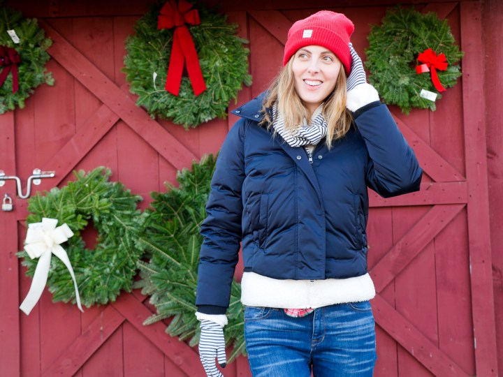 Eva Amurri Martino wears a navy puffer jacket, blue jeans, and a red hat and stands in front of a selection of wreaths at a Christmas Tree Farm