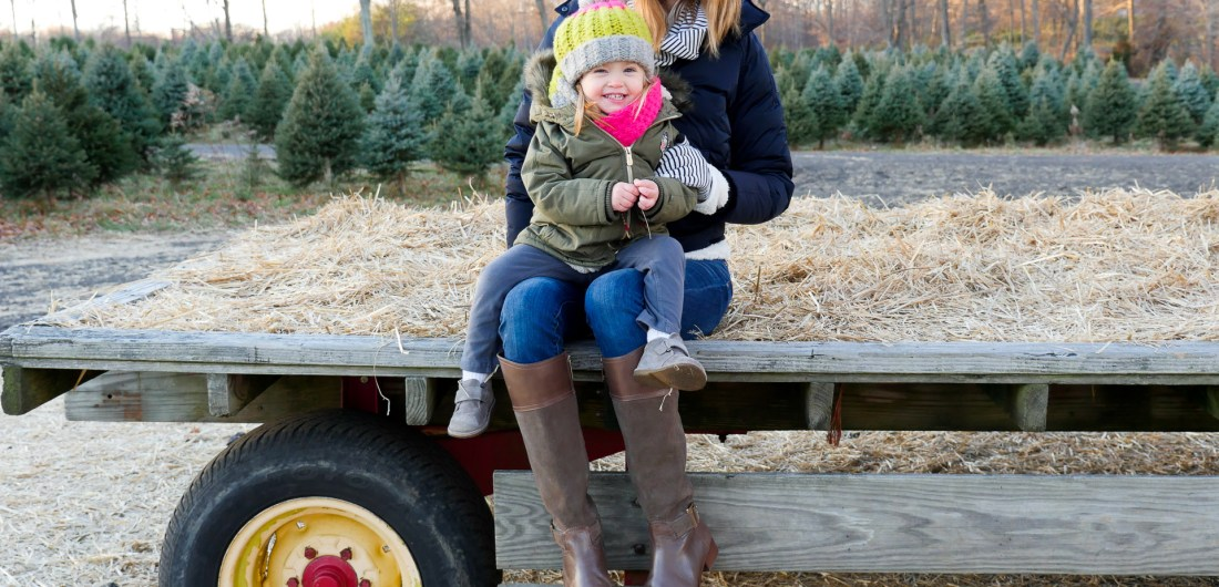 Eva Amurri Martino of lifestyle and Motherhood blog Happily Eva After takes her daughter Marlowe on a hay ride at the christmas tree farm in Connecticut