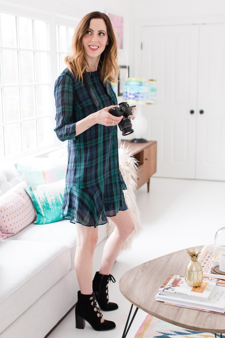 Eva Amurri Martino wears a plaid shift dress and black boots while she shoots with her camera in her studio in Connecticut.