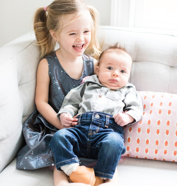Marlowe Martino holds baby brother, Major, while wearing a sparkly grey dress and pigtails