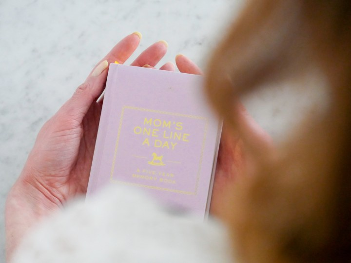 Eva Amurri Martino hold a lavender memory book in her hands