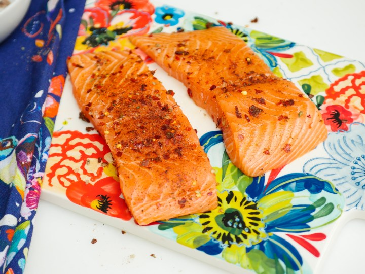 Raw salmon sits on the colorful cutting board with the Mexican Spice rub applied