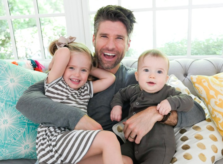 Kyle Martino holds two year old daughter, Marlowe, and seven month old son, Major, on his lap at their home in Connecticut