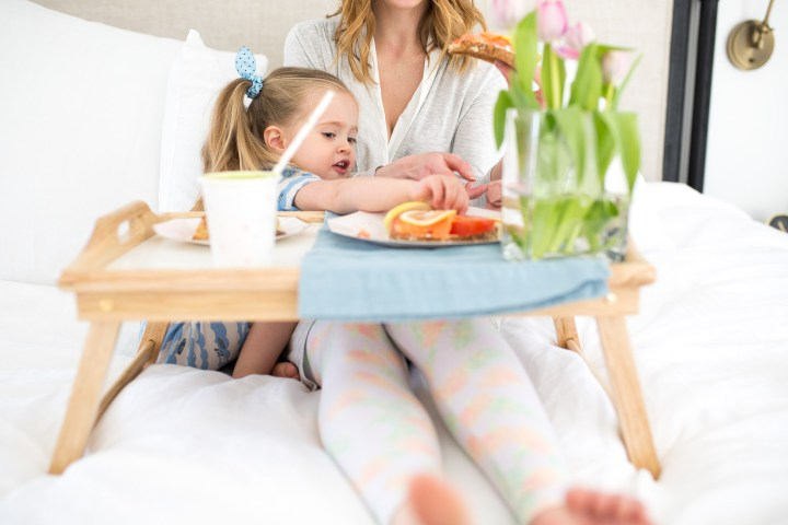 Marlowe Martino sits on her Moms lap for a Mother's Day breakfast in bed