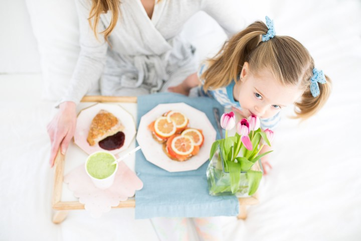 Marlowe Martino smells a bouquete of flowers on a mother's day breakfast tray
