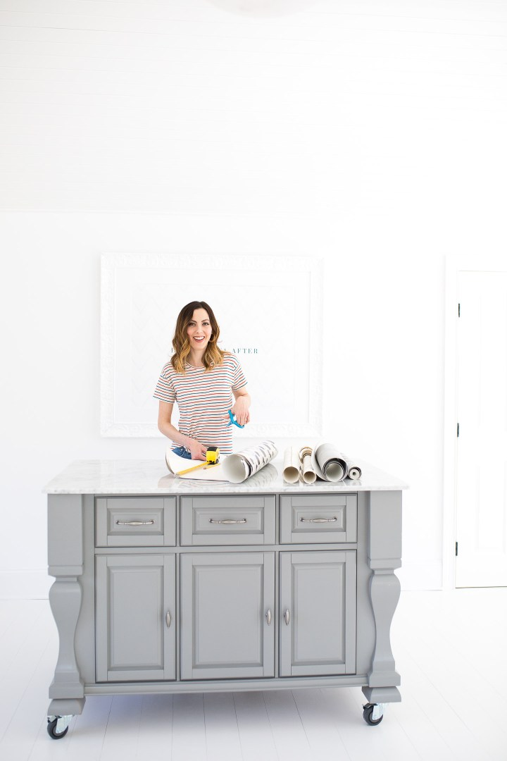 Eva Amurri Martino measures wallpaper in her studio to use for leftover wallpaper projects around the house