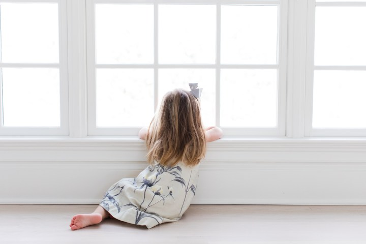 Marlowe Martino wears a floral dress and grey hair bow and looks out the window
