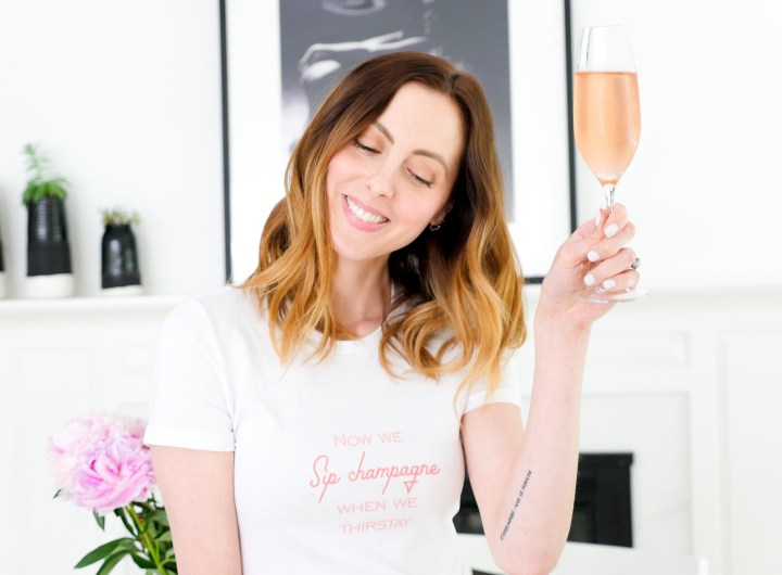 Eva Amurri Martino raises a glass of rosé champagne in her custom shirt designed by The Happily App