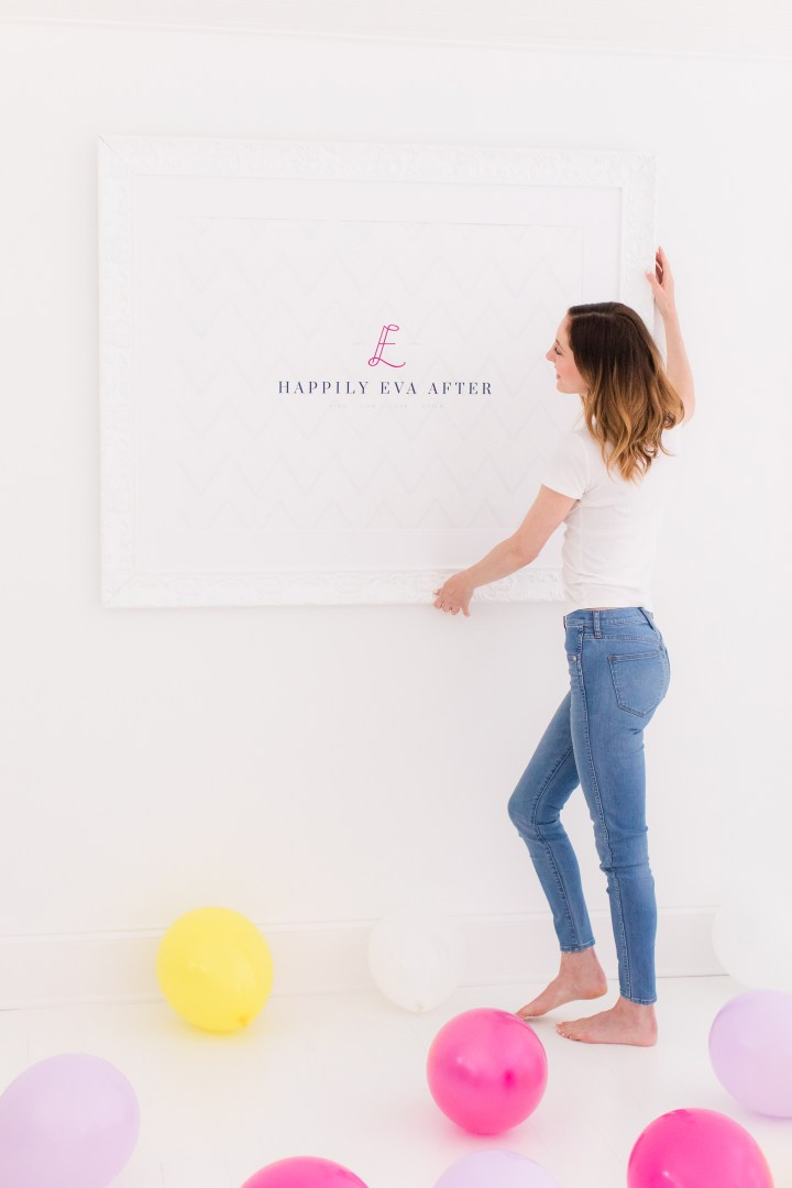Eva Amurri Martino hangs up a framed poster of the Happily Eva After logo on her studio wall