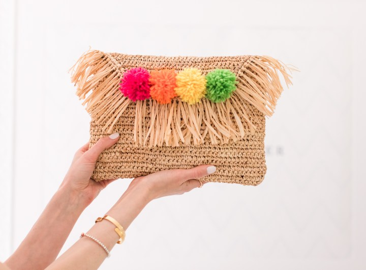 Eva Amurri Martino holds up a multicolored DIY pom pom straw clutch