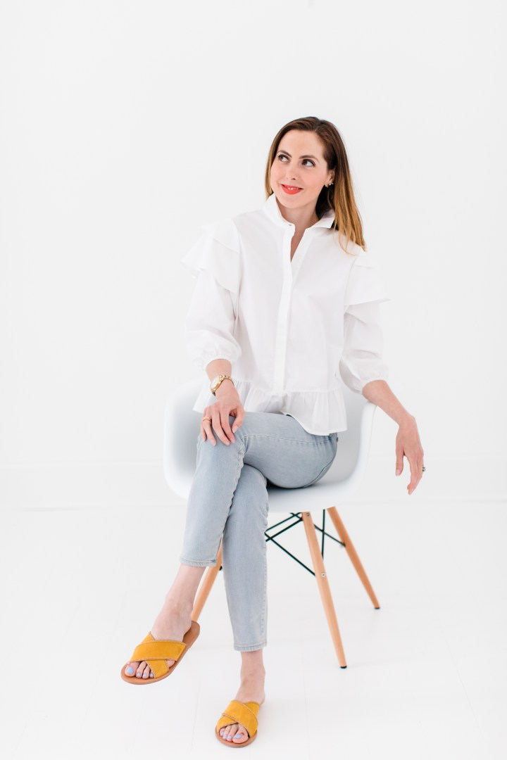 Eva Amurri Martino wears a white button down shirt with ruffle details and jeans with flats