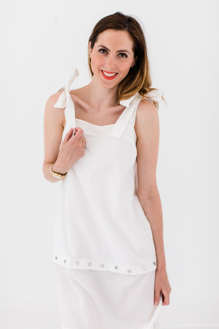 Eva Amurri Martino wears an adjustable white snap dress with bow straps as part of a post about packing simply