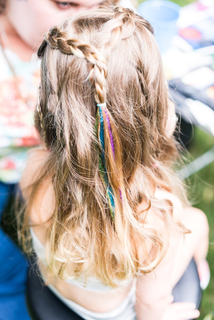 Marlowe Martino gets glitter painted in her hair at the mermaid braid bar at her third birthday party