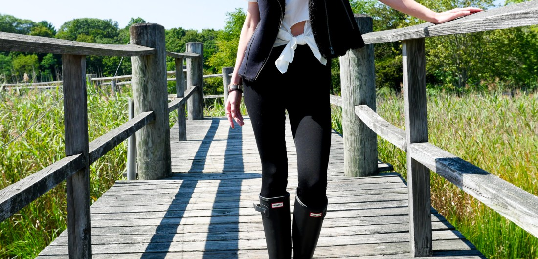 Eva Amurri Martino wears black Hunter wellington rain boots and black leggings as she stands on a bridge in Connecticut