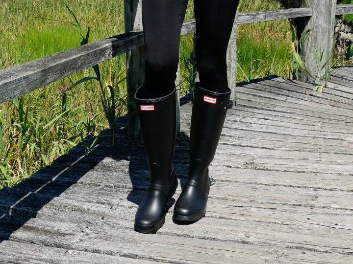 Eva Amurri Martino wears black Hunter wellington rain boots and black leggings as she stands on a bridge in Connecticut