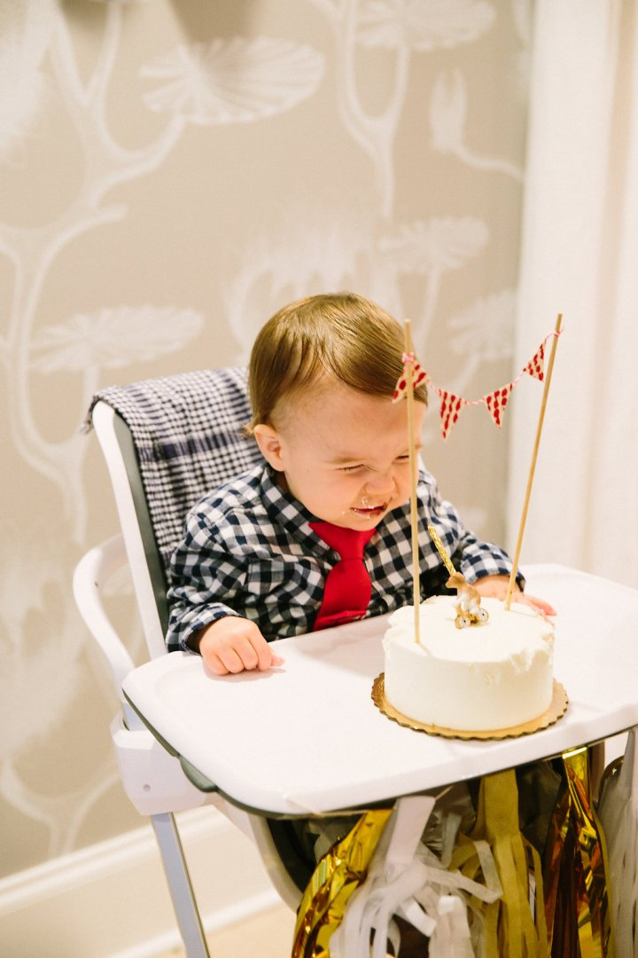 Major laughs as he sits in front of his first birthday cake