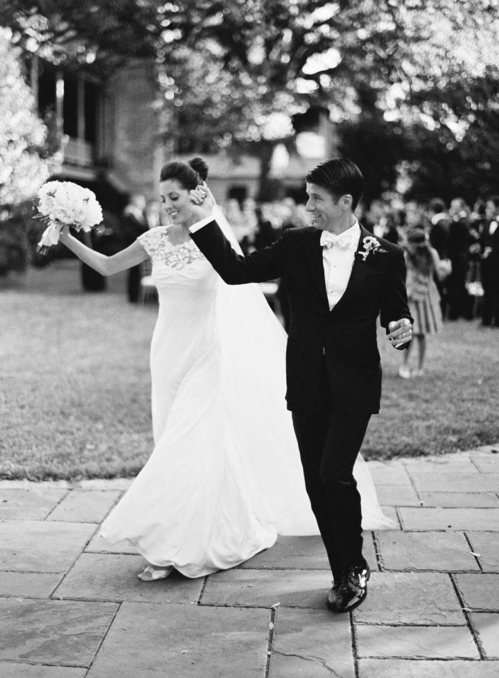 Eva Amurri Martino and Kyle Martino walk through a courtyard after their wedding ceremony in Charleston SC