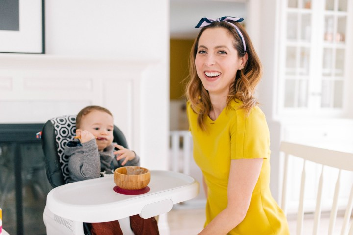 Eva Amurri Martino wears a yellow dress and oversees her son Major eating a bowl of porridge with a SpoonfulOne mixin