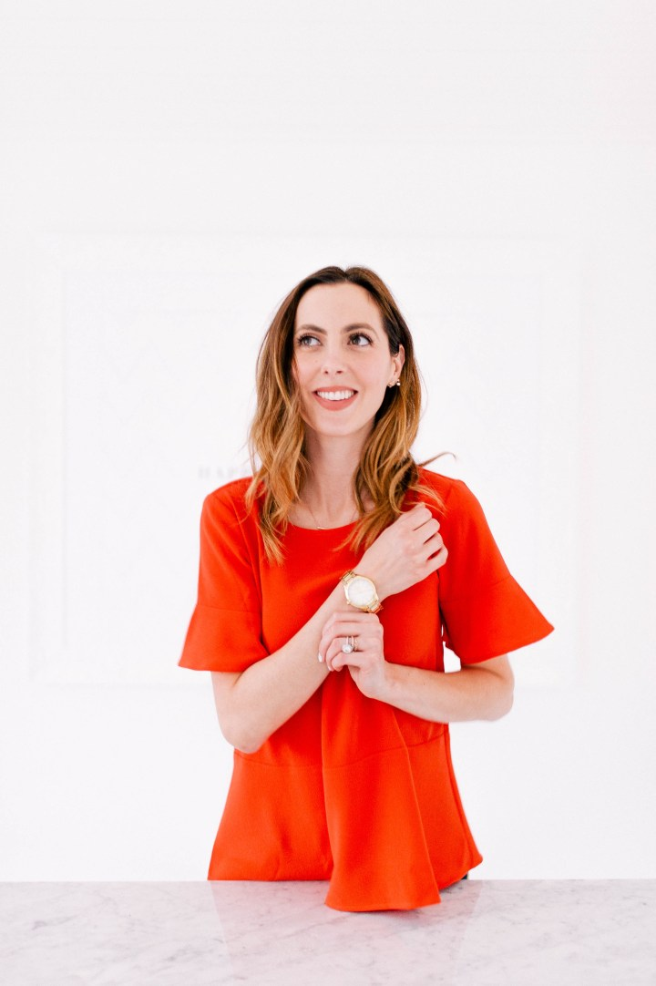 Eva Amurri Martino puts on her gold Tory Burch watch, pairing it with a red fluter top and navy blue flower patterned pants