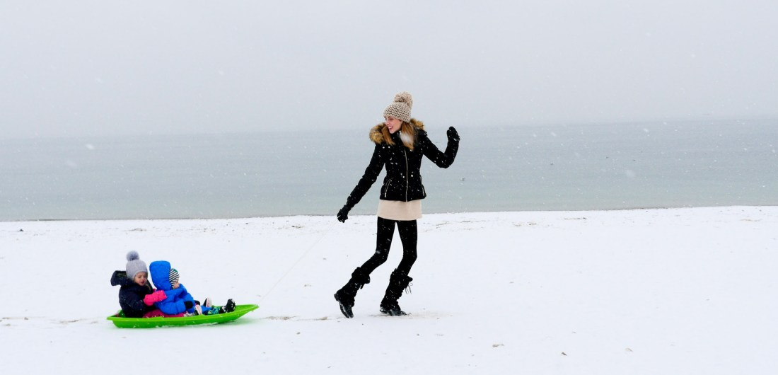 Eva Amurri Martino pulls her children through the snow on the beach in Westport, CT