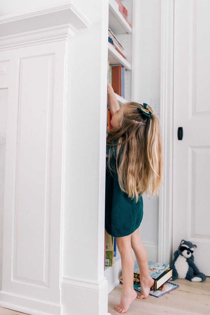 Marlowe Martino wears a hunter green dress and reaches up to pull a book from the book shelf at her home in Connecticut