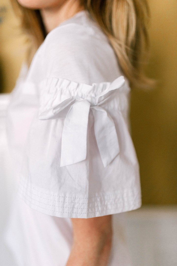 Detail of a white classic shirt with bow detail on the sleeve