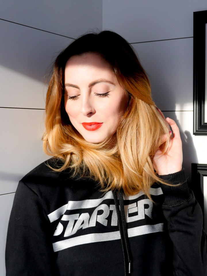 Eva Amurri Martino wears a Starter hoodie with red lipstick and stand in a beam of sunlight