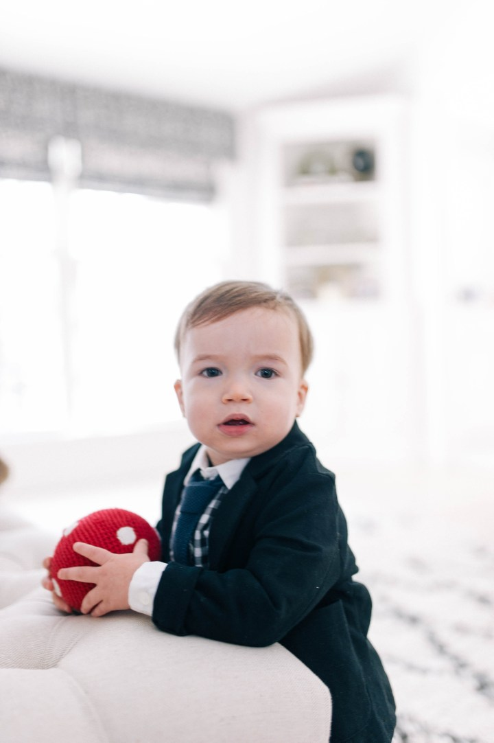 Major James Martino wearing a holding a navy blue suit with a gingham shirt and holding a red ball in his Connecticut home