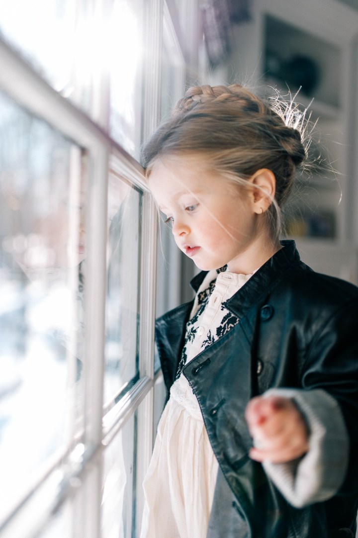 Marlowe Mae Martino looks out the window of her Connecticut home wearing a halo braid.