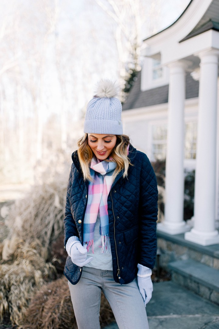 Eva Amurri Martino wears a navy quilted jacket, pastel plaid scarf and a pompom hat in the garden of her Connecticut home