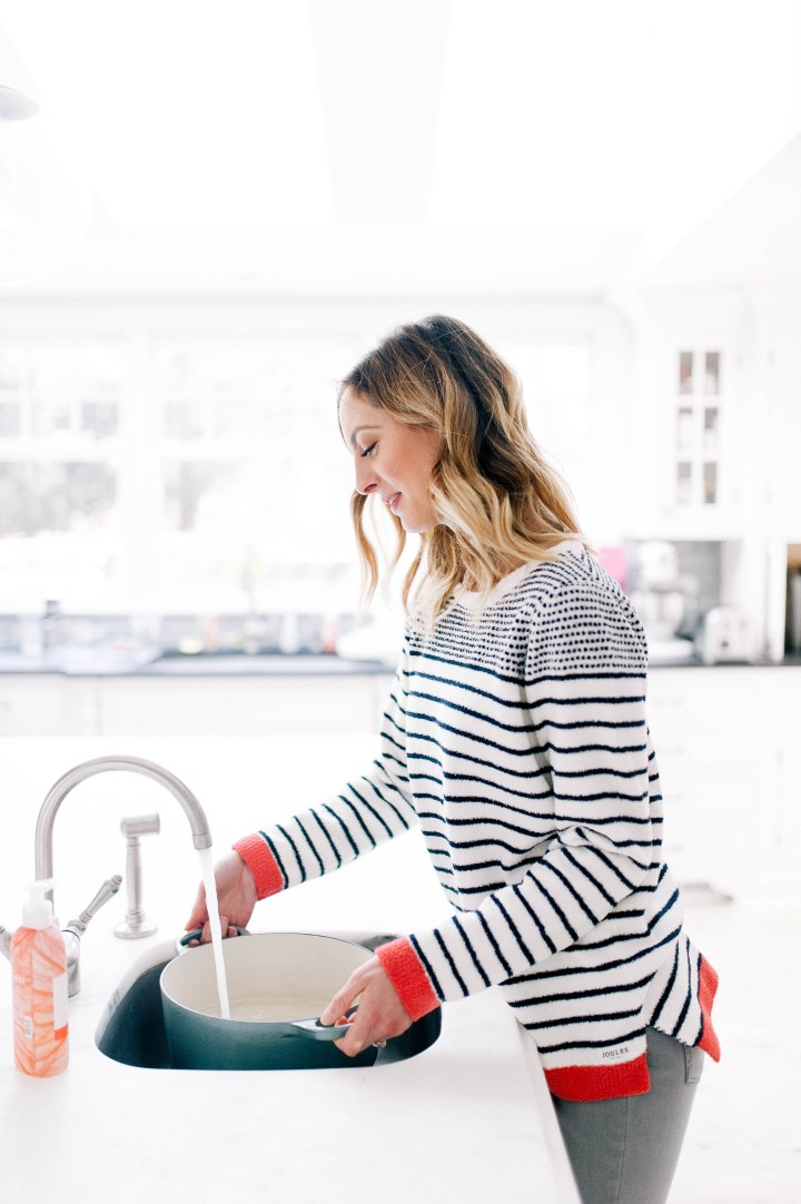 Eva Amurri Martino wears a cozy striped sweater and fills up a pot of water at the kitchen sink