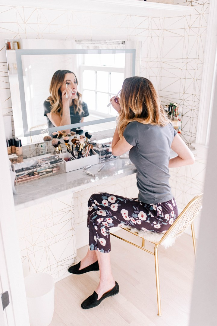 Eva Amurri Martino sits in the glam room of her Connecticut home, wearing floral pants and a grey tshirt, and fills in her eyebrows with an eyebrow pencil