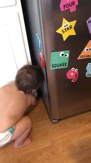 Activities for infants and toddlers playing with shape and number magnets on the refrigerator