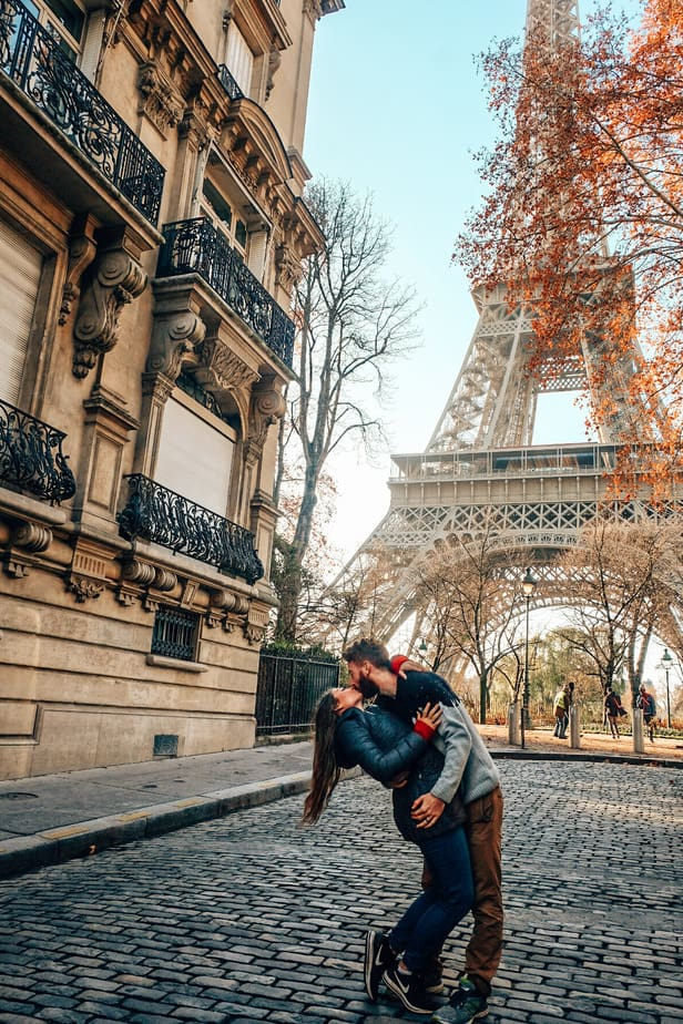 a couple kissing in front of the eiffel tower in Paris.