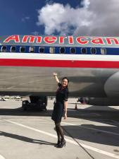 Flight attendant posing in front of American Airlines plane