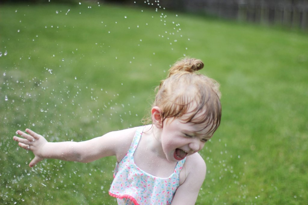 Blaire playing in sprinkler
