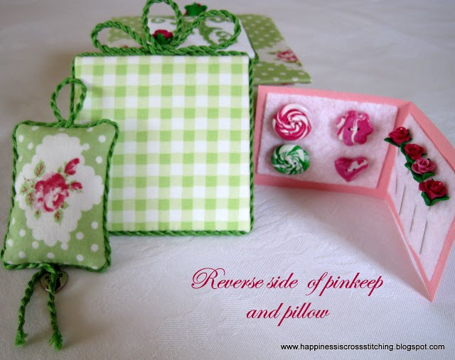 Cross stitch covered box decorated with green fabric and pink roses in the design with matching pin keep and small pillow