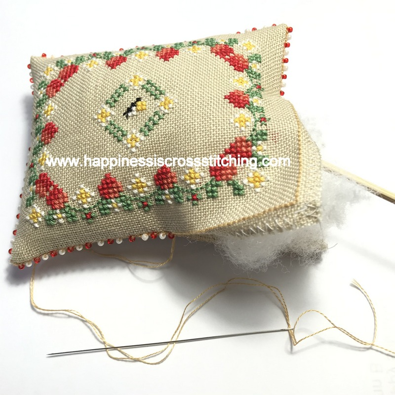 Filling a cross stitched pillow with fibrefill