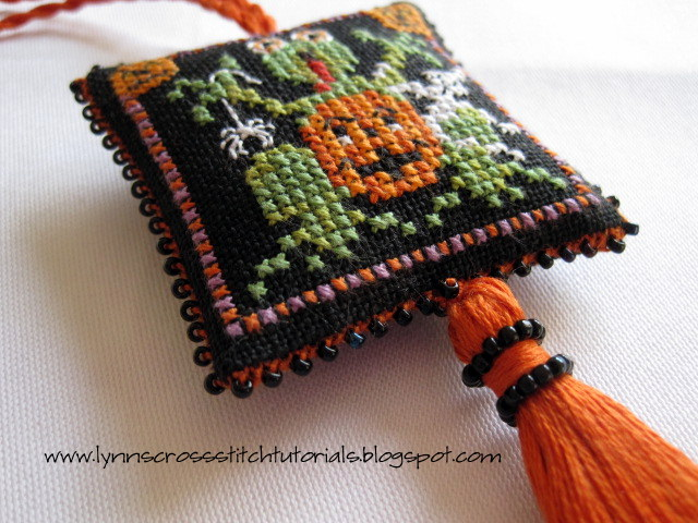 Beaded cross stitched scissor fob with Spooky green frog, a pumpkin , a ghost and a spider.