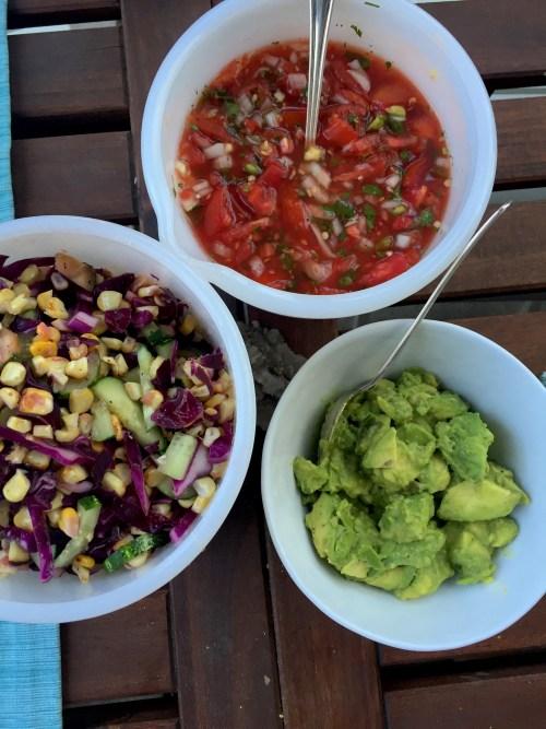 Trio of bowls with pico de gallo, guacamole, and a salad of cabbage, zucchini, cucumber, and corn
