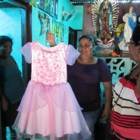 Maria zeigt eines ihrer selbstgeschneiderten Kleider