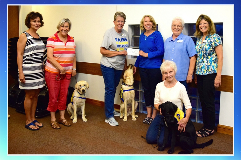 Canine Companions for Independence Kansas City chapter puppy raisers and volunteers standing with three dogs in training as chapter president accepts donation check from Happy-Go-Doodle founder who won a donation to non-profit as part of BlogPaws Best New Pet Blog win