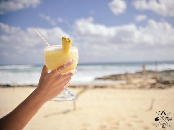 woman holding cocktail on beach on staycation